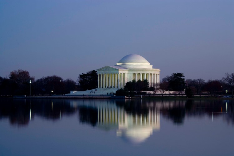 Jefferson Memorial lit up at night with reflection in the tidal pool