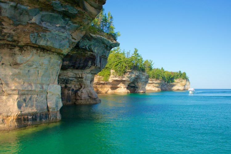 Crystal clear blue waters along the cliffs at Pictured Rocks National Seashore in summer