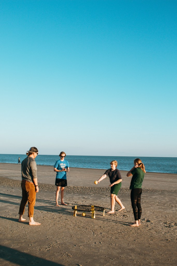 family on the beach playing Spikeball