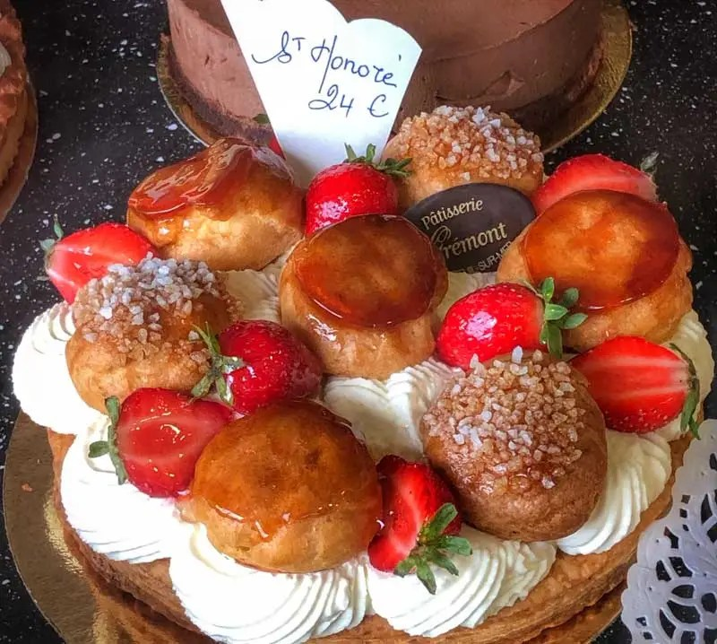 Saint Honore cake in a shop in France, strawberries, cream puffs, cream on a bed of puff pastry