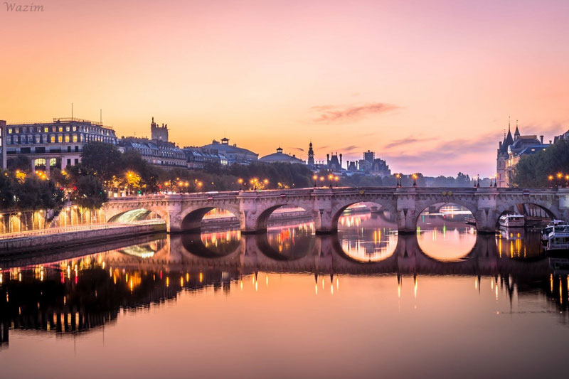 View of Paris at sunset, pink sky reflected in the River Seine