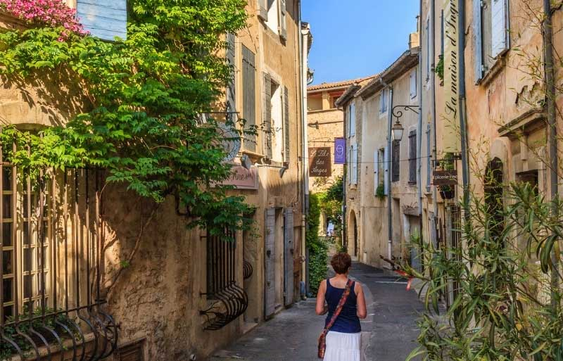 Woman wanders along a street in Lourmain, Provence, houses dripping with flowers