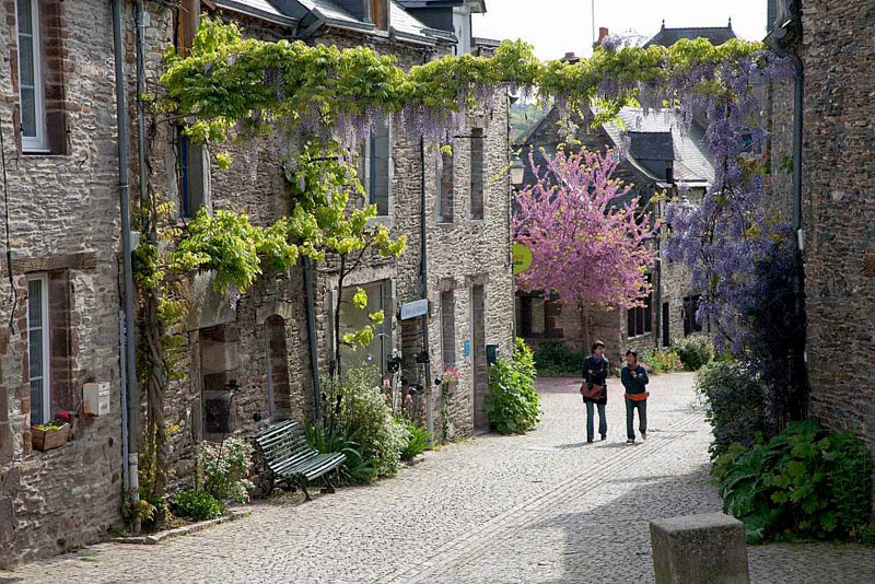 Two women walking along a cobbled street, spring flowers in blossom, Morbihan, Brittany