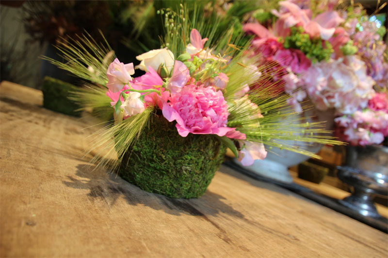 Floral display of pink flowers and green grasses in the gardeners workshop at Castle of Chenonceau