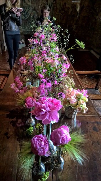 People take photos on their mobile phones of an exquisite display of flowers on a table