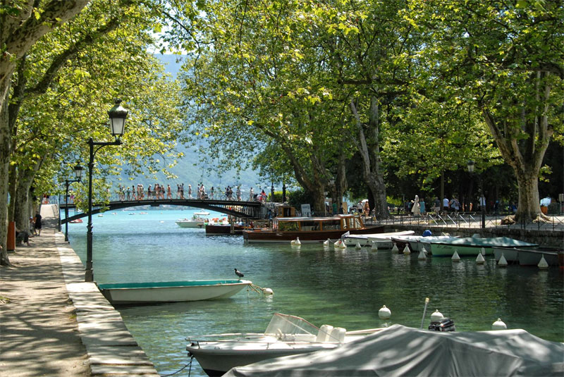 Canal in Annecy, people crossing a narrow bridge and boats bobbing gently