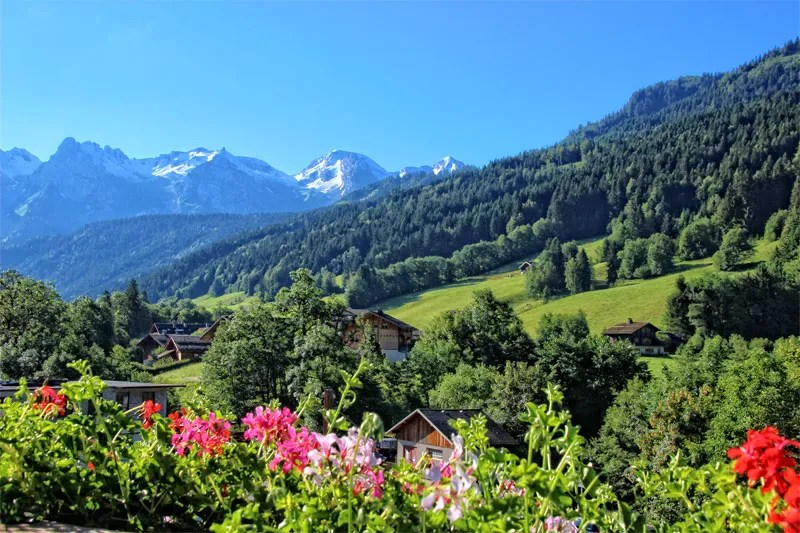 Mountains topped with snow in summer, meadows of flowers under a sunny sky, Annecy Mountains