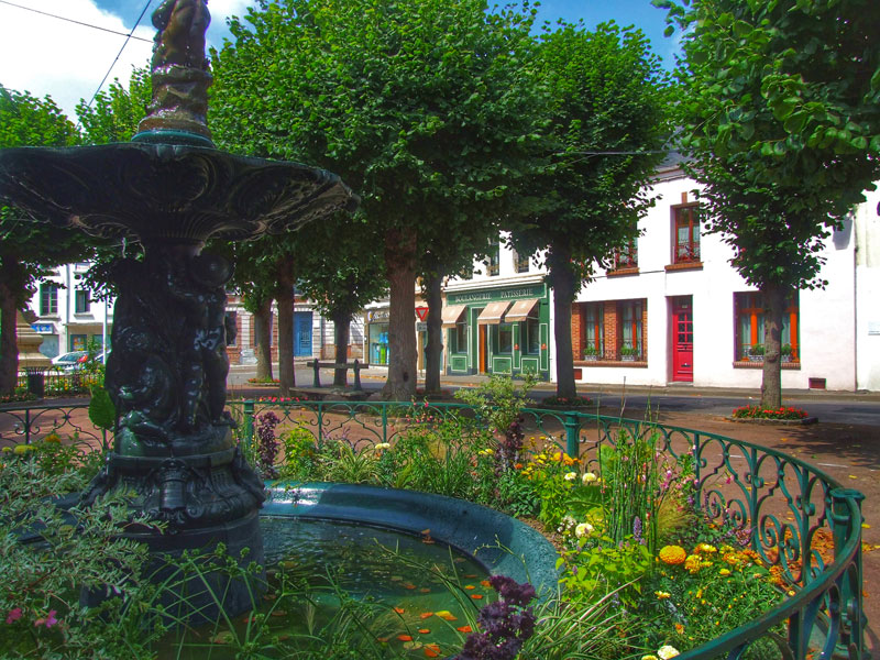 Pretty fountain in a town square lined with bakeries and colourful little shops in Montreuil-sur-Mer
