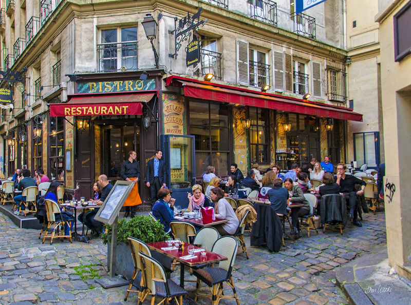 Bistro in Paris with people sitting outside at tables and chairs on the pavement