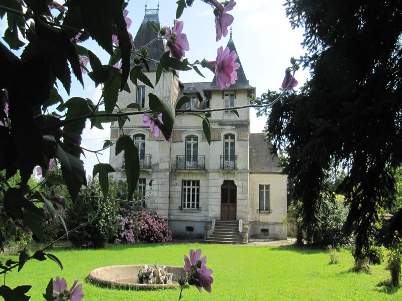 Pretty Chateau of white stone with black slate roof and turrets