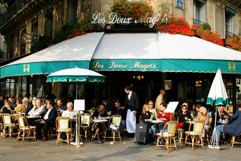 People sitting outside a cafe with a green awning being served by waiter in a suit with bow tie and traditional apron