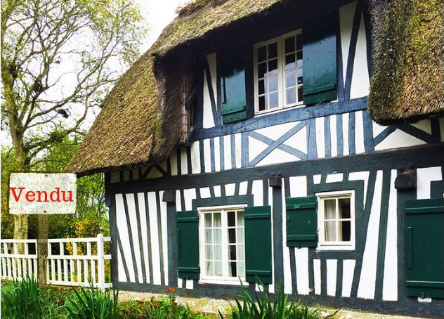 """Half-timbered house with white walls and green wood panels with a """"Sold"""" Sign"""