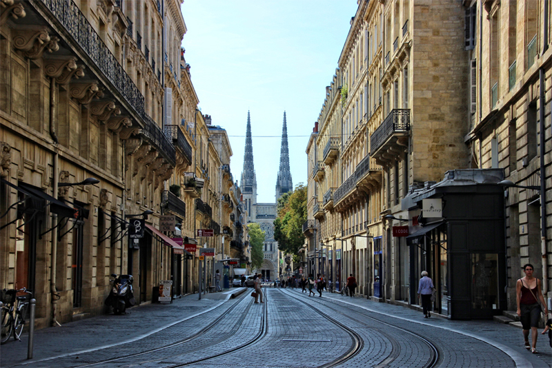 Tram lines run down the middle of a road lined with neoclassical style buildings in Bordeaux, church towers in distance