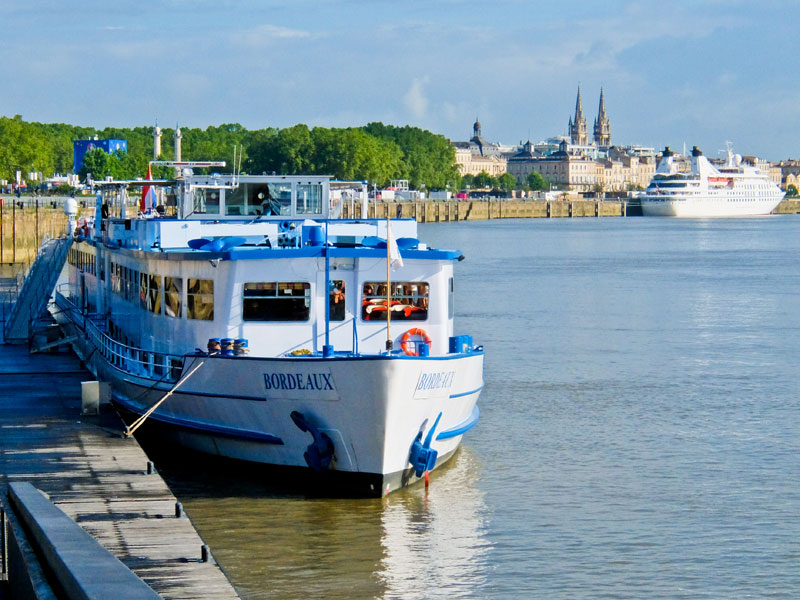 A boat called Bordeaux floats on the river in Bordeaux city centre