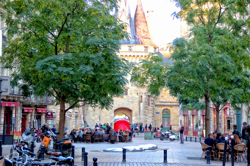 An elegant square in the city of Bordeaux, lined with tables and chairs outside restaurants with leafy trees