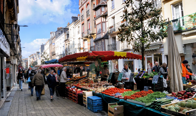 Busy market place in a street lined with tall houses in the port town of Dieppe, Normandy, France