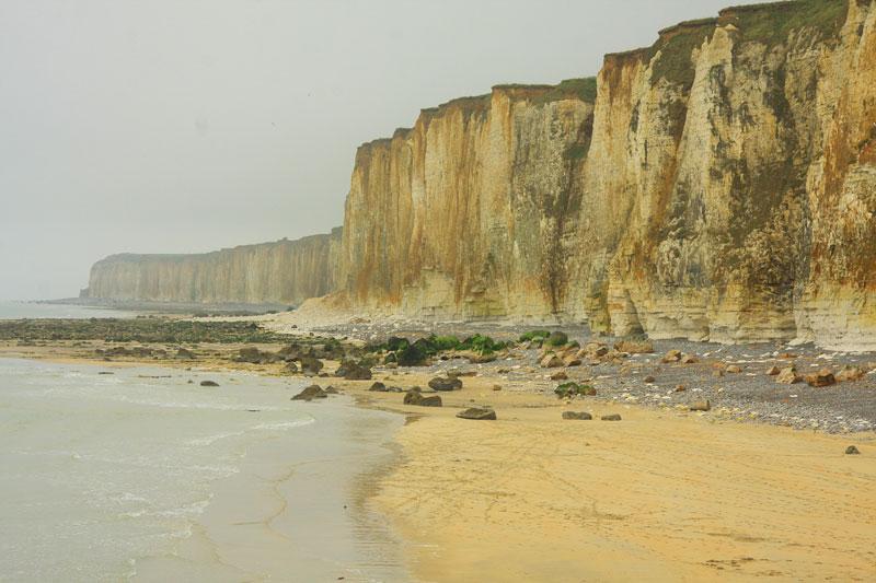 Monumental cliffs loom over a sandy beach on the coast of Normandy France