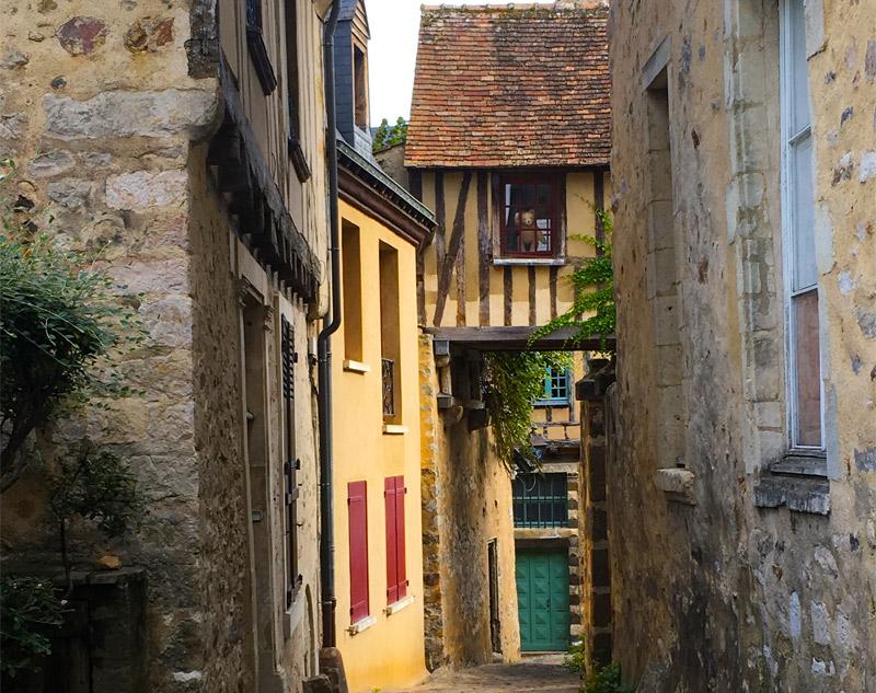 Ours en peluche vagues d'une fenêtre d'une maison à colombages dans une rue pavée du Mans