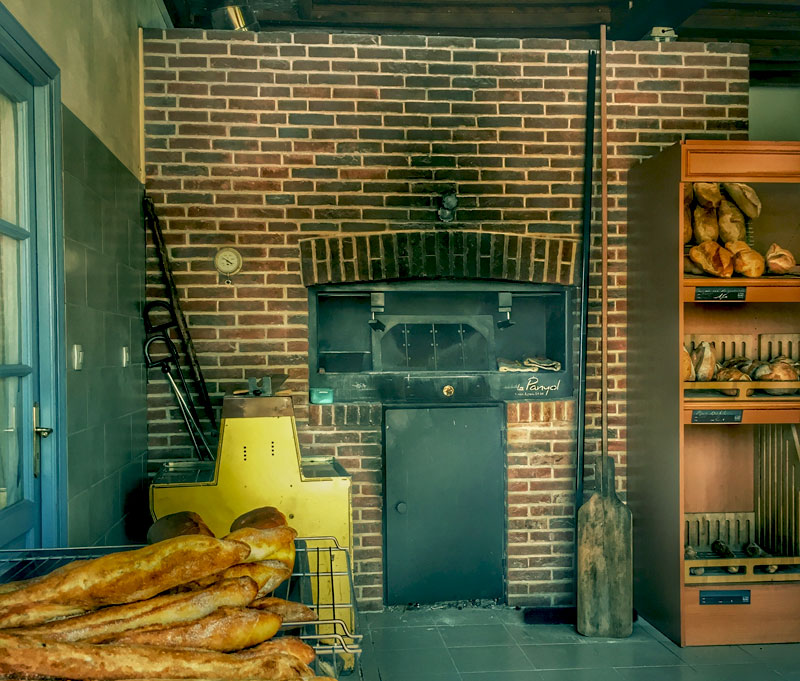 Wood oven set into a stone wall in a French bakery, baguettes just pulled out, still steaming