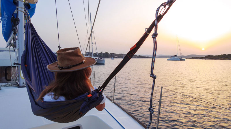 Woman relaxes in a hammock on the deck of a boat at sunset, perfect sailing holiday experience