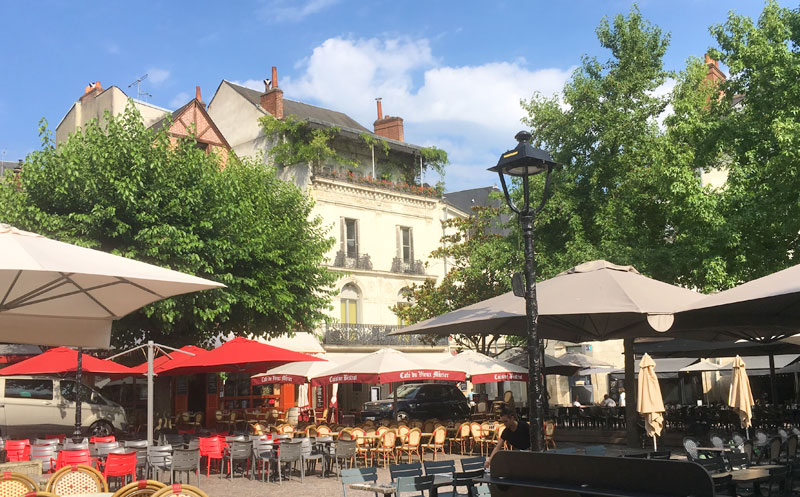 Sunlit square lined with trees and filled with tables and chairs with bright parasols, city of Tours, Loire Valley