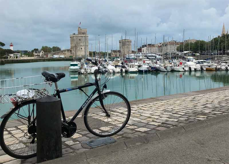 Bike parked at the side of the port at La Rochelle, the sky cloudy, the water bright blue