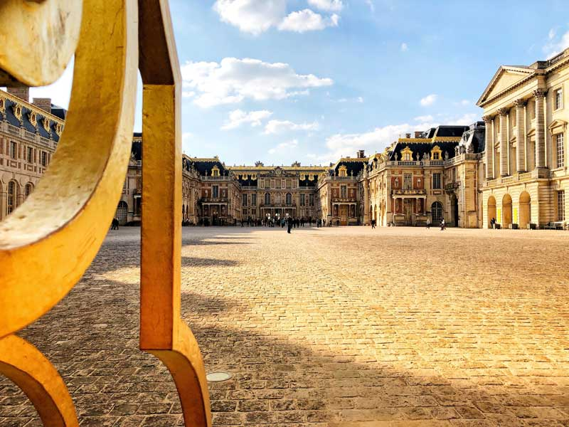 Front facade of the Palace of Versailles, yellow stone, black slate roofs, gilded windows, golden gates