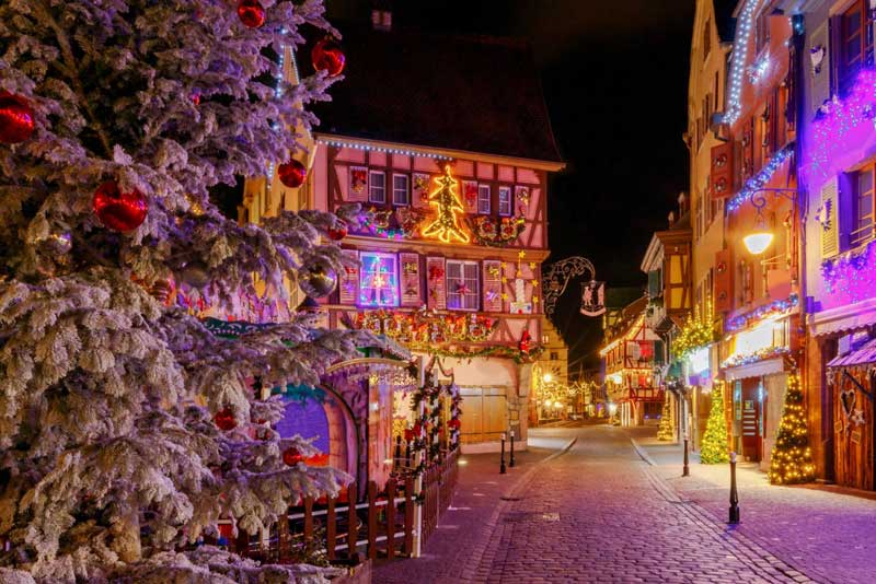 A cobbled street, half timbered houses decorated for Christmas, Colmar, Alsace, France