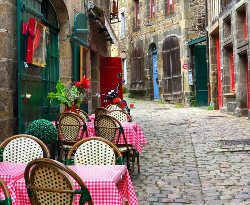 Tables covered with red and white check cloths outside a restaurant on a cobbled street in Dinan