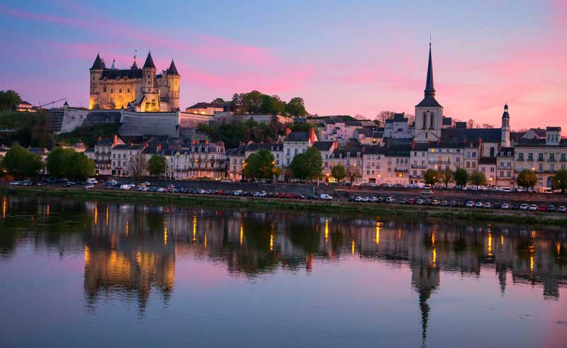 Saumur in the Loire Valley at dusk, the castle of Saumur sits high on a hill dominating the town