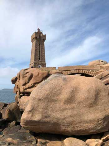 Pink granite boulders and light house along the Pink Granite Coast of Brittany