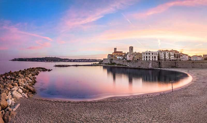View of the bay in Antibes southern France under a pink sunset