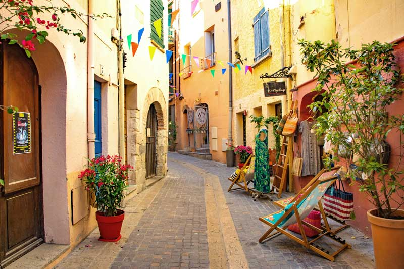 Cobbled stret in Collioure, lined with boutiques and art galleries, bunting hangs, flowers in pots