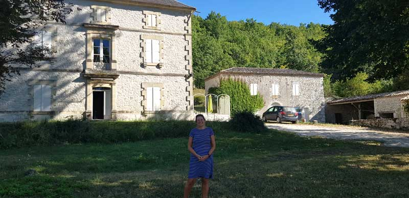 Woman stands in front of traditional style white stone house