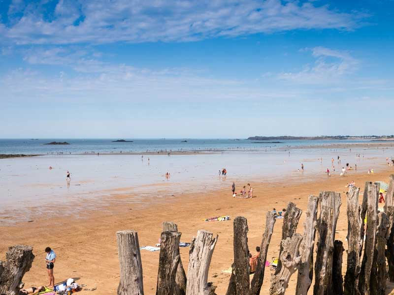 Sandy beach of St-Malo, people paddling in the sea and relaxing in the sun