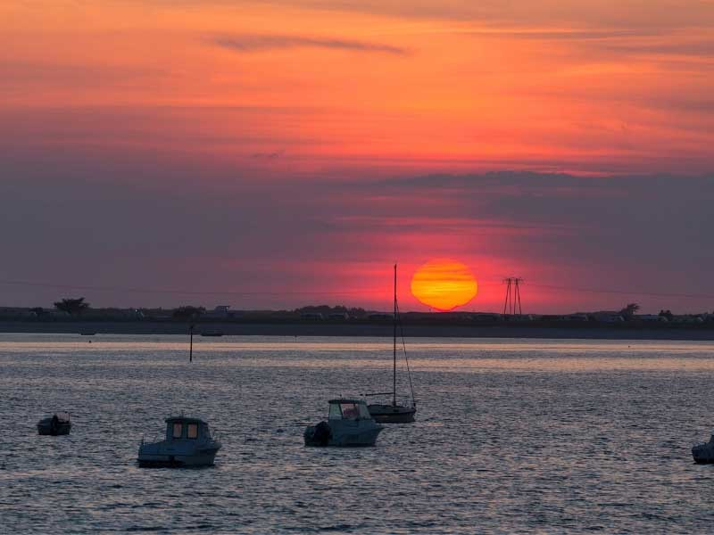 View of the sea at sunset, small boats bobbing, at the seaside town of Carnac Plage, Brittany