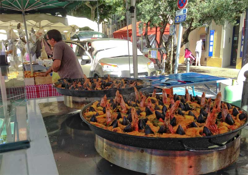Street food at Carpentras market, a vast pan of seafood and rice under a green awning