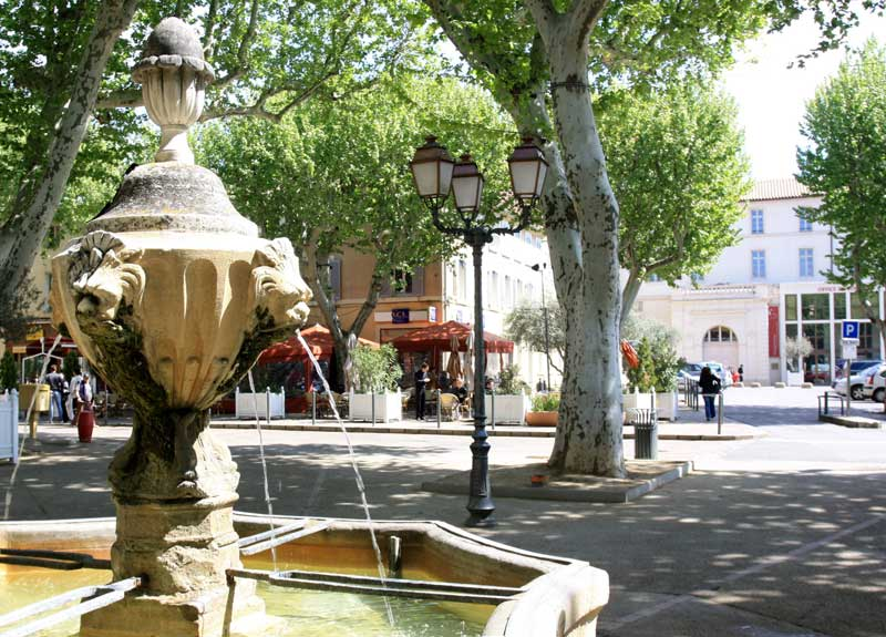 Fountain spewing water in a cobbled street lined with plane trees in Carpentras, Provence