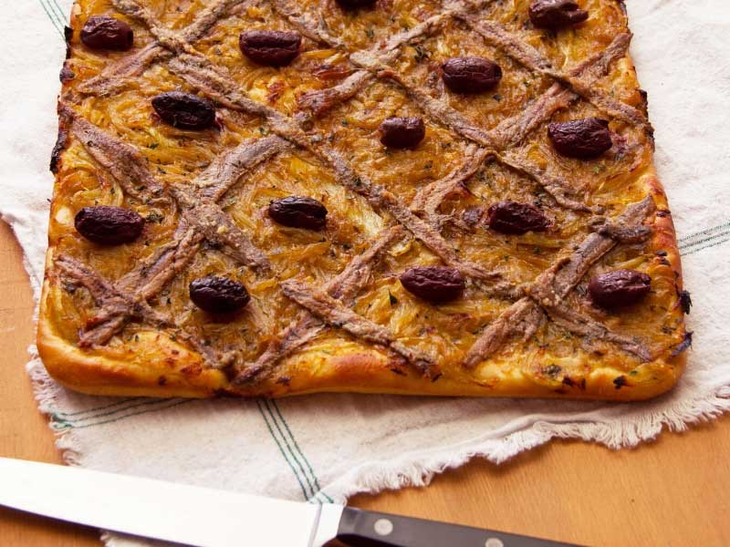 Southern French style pizza called pissaladiere, bread dough base piled with onions, olives, anchovies