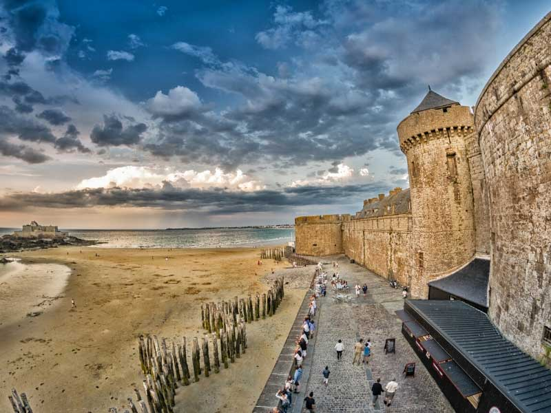 Walls of the port town of St-Malo, Brittany, dotted with towers, a sandy beach at its feet