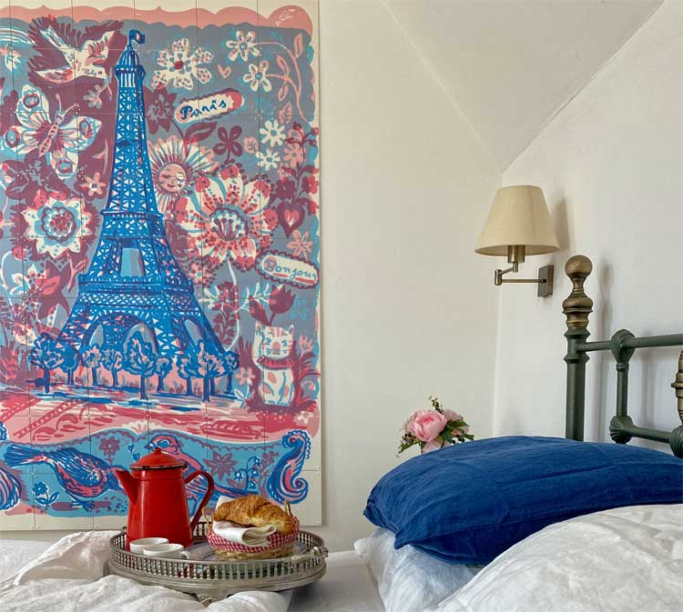 Bedroom with a large reproduction painting of the Eiffel Tower in pastel colours
