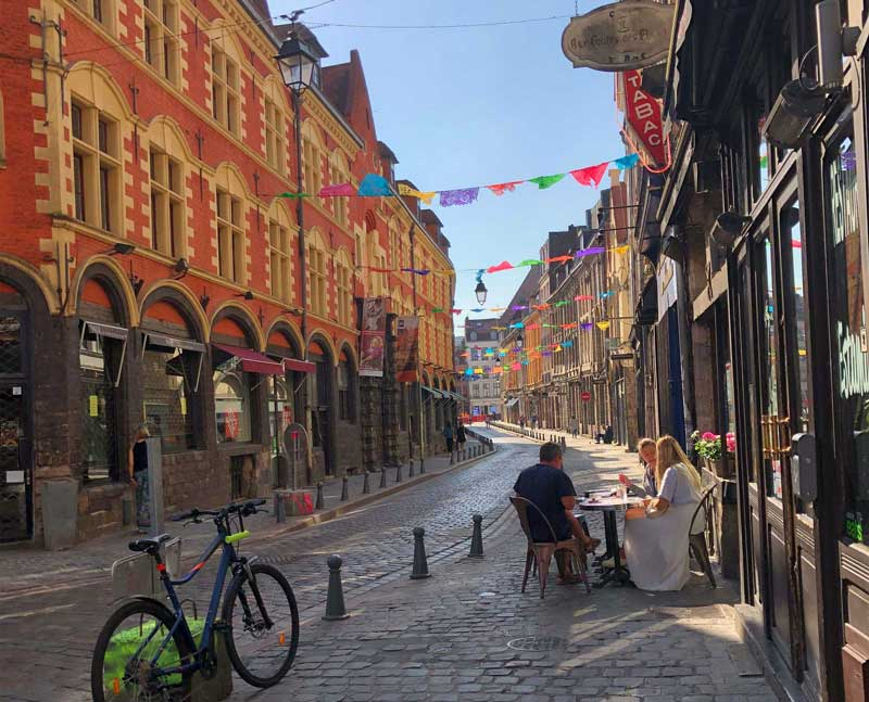 Cobbled street in Lille, people sitting at a cafe enjoying the sun and the bunting across the street