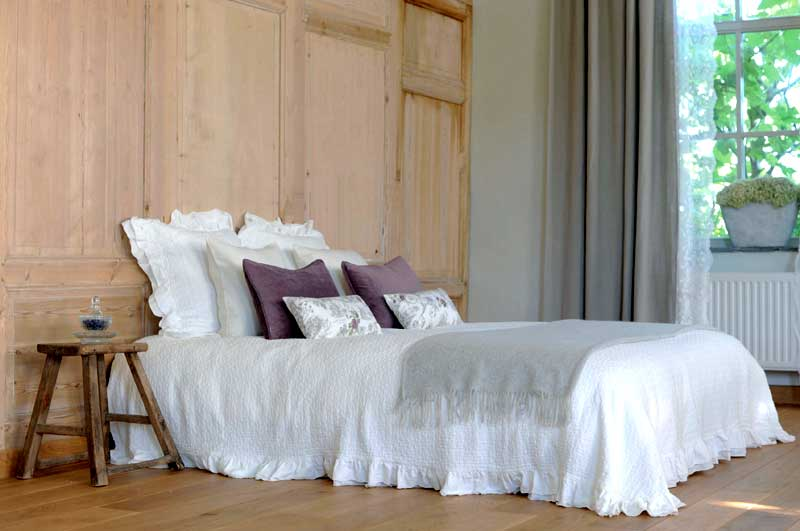Bed with luxurious white bed cover, cushions and a soft throw