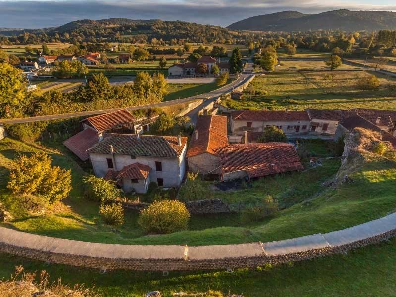 Aerial view of houses surrounded by grassy hills and mountains in Haute Garonne France