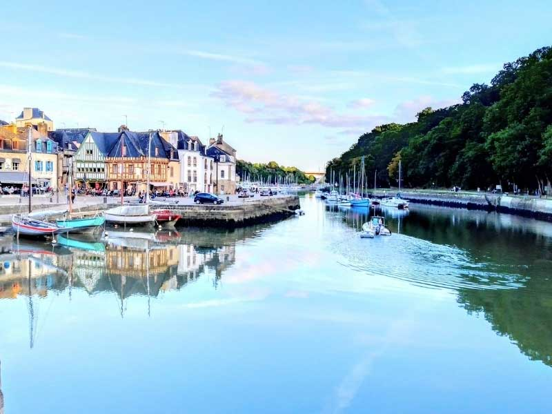 Half-timbered houses and shops alongside a gentle river in Morbihan