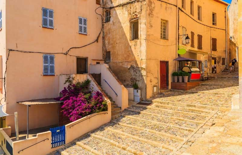 Ancient buildings of mellow sun-baked stone along a cobbled street in Corsica