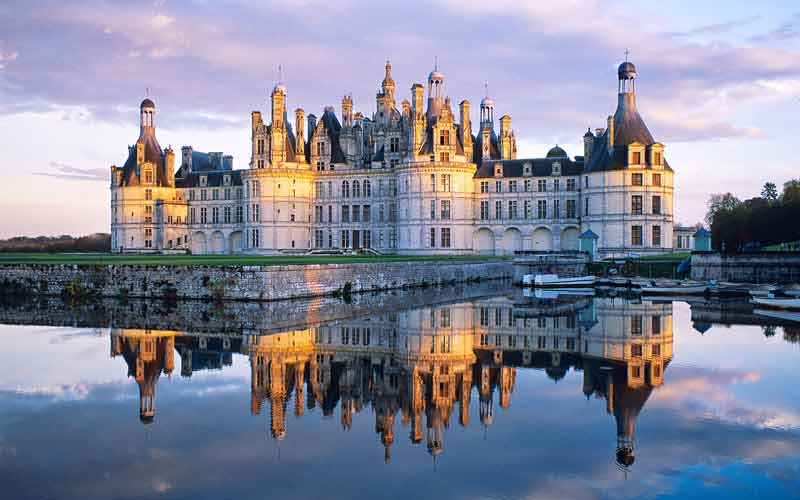 Chateau de Chambord at dusk, pink sky reflected in river