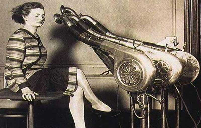 Woman sits in front of a huge hairdryer, a French invention
