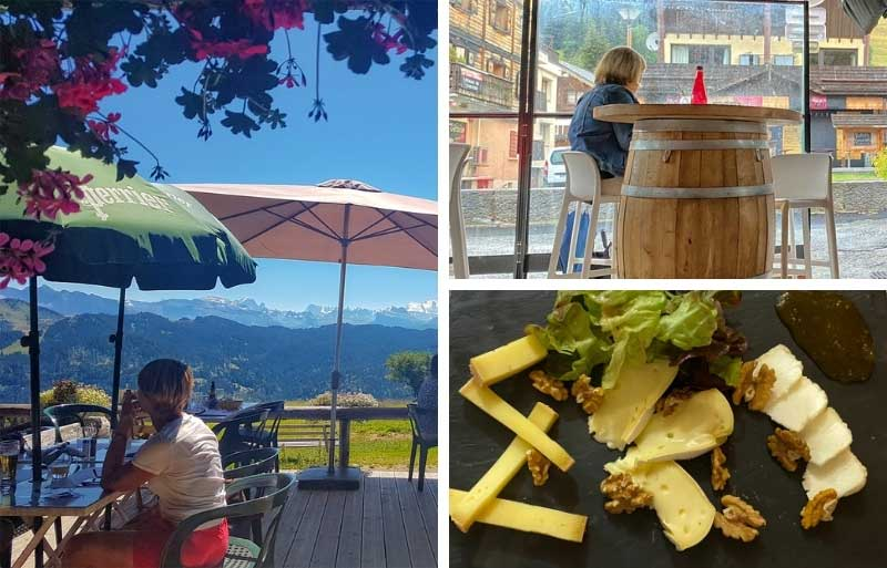 Woman sits at a table in a mountain restaurant overlooking mountains in Les Gets