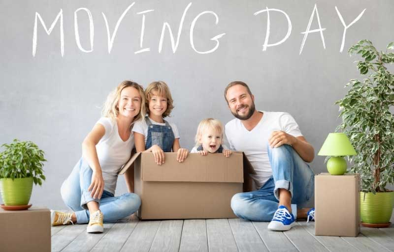 Family sit with moving boxes waiting to move home